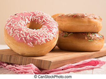 Delicious donuts with icing on wooden panel