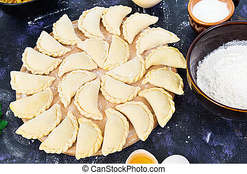 Delicious dumplings with cabbage on dark background
