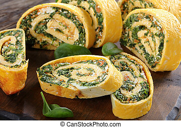 delicious egg roulade with greens, close-up