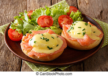 Delicious eggs benedict with smoked salmon, hollandaise sauce and fresh vegetables close-up on a plate. horizontal
