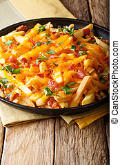 Delicious fast food: French fries with cheddar cheese, bacon and herbs close-up. vertical