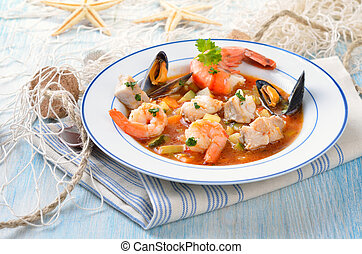 Delicious fish soup with shimps, mussels, fish fillet and vegetables