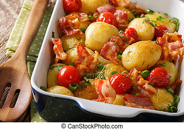 Delicious food: fresh potatoes baked with bacon, green onions and tomatoes macro. horizontal
