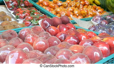 Delicious fresh fruits on the street market counter under a special cellophane cloth, protected from dust and moisture. Peaches, Nectarine, apricots, strawberries, kiwi