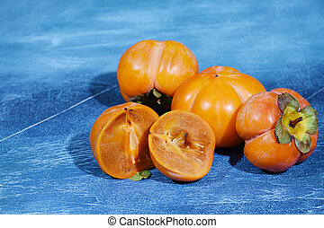 Delicious fresh persimmon fruit on the brigth blue background. Horizontal.