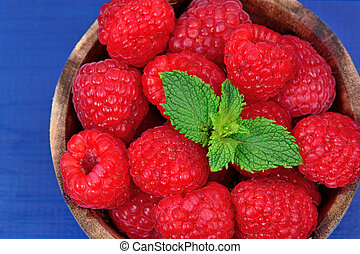 Delicious fresh raspberries in a bowl on wooden table