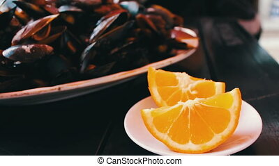 Delicious freshly prepared mussels lie on plate on a table in a restaurant