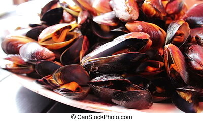 Delicious freshly prepared mussels lie on plate on a table...