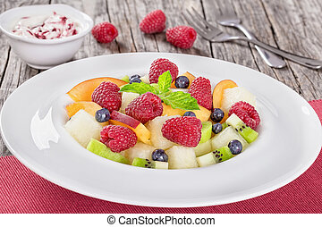 delicious fruit and berry summer salad decorated with mint...