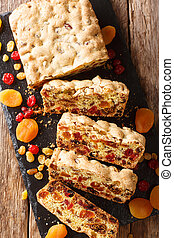 Delicious fruit bread with dried apricots, raisins, figs, cherries closeup on a slate board. vertical top view