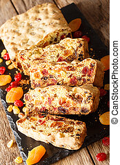 Delicious fruit bread with dried apricots, raisins, figs, cherries closeup on a slate board. vertical