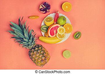 Delicious fruit mix with pineapple, orange, lime, kiwi, banana, pomegranate on vintage orange background.