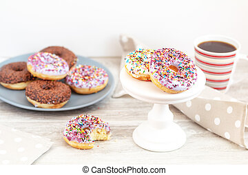Delicious glazed donuts and cup of coffee on light wooden...