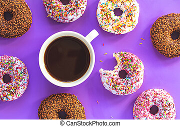 Delicious glazed donuts and cup of coffee on violet surface