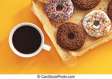 Delicious glazed donuts and cup of coffee on yellow surface