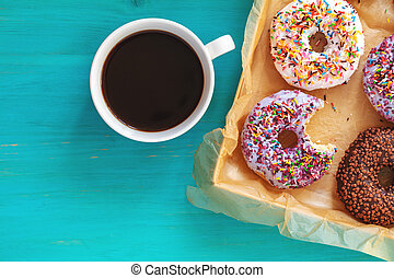 Delicious glazed donuts in box and cup of coffee on turquoise blue surface
