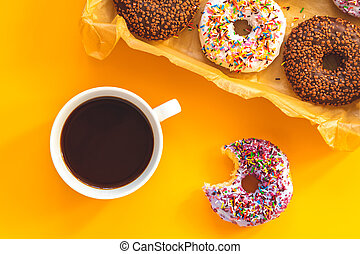 Delicious glazed donuts in box and cup of coffee on yellow surface