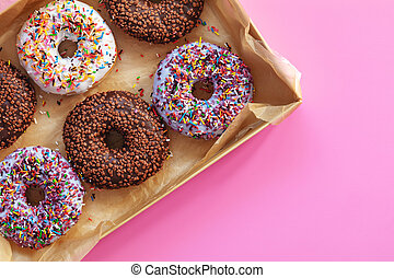 Delicious glazed donuts in box on pink surface