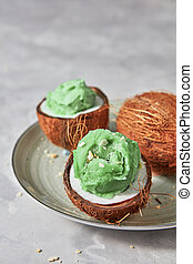 Delicious green ice cream in a coconut shell on a plate on a gray concrete background.