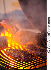 Delicious grilled beef steak with fire on background