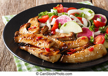 Delicious grilled king oyster mushrooms and salad of radishes and tomatoes close-up. horizontal