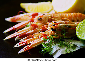 Delicious Grilled Langoustines on Newspaper with Lime and Lemon closeup on Dark Wooden background. Focus on Animal Eyes on Foreground