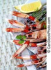 Delicious Grilled Langoustines with Lemon and Greens on Newspaper closeup on Wicker background. Selective Focus
