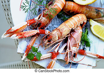 Delicious Grilled Langoustines with Lemon and Parsley on Newspaper closeup on Wicker background. Top View