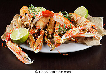 Delicious Grilled Langoustines with Lime and Rosemary on White Plate closeup on Dark Wooden background