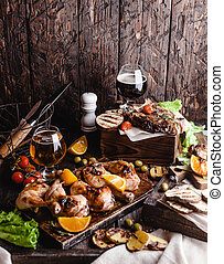 delicious grilled meat with vegetables and beer on wooden background