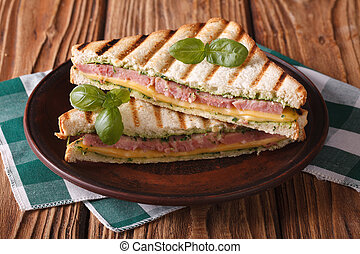 Delicious grilled sandwich with ham, cheese and basil