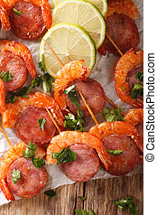 Delicious grilled shrimp with chorizo on skewers and herbs closeup on the table. vertical top view
