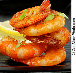 Delicious Grilled Shrimps with Lemon and Thyme closeup on Black plate