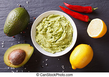 Delicious guacamole sauce and ingredients. horizontal top view