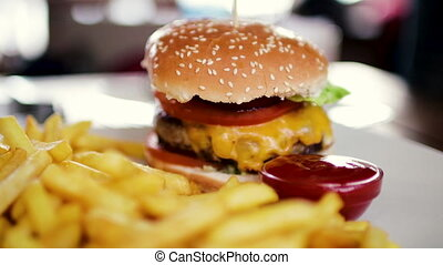 Delicious hamburger with a big chop and a jar of french fries with ketchup