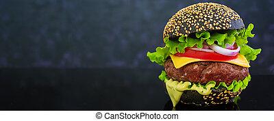 Delicious handmade burger on dark background. Banner.