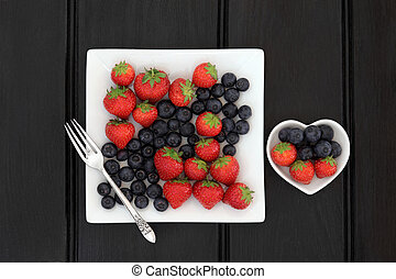 Strawberry and blueberry fruit in square and heart shaped porcelain dishes and old silver fork.