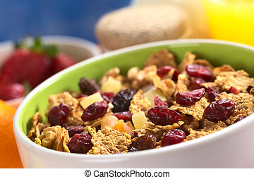 Delicious healthy breakfast with a bowl full of wholewheat flakes mixed with dried fruits (cranberries, bananas, raisins and some others) and nuts with fresh fruits, yogurt and orange juice around (Se