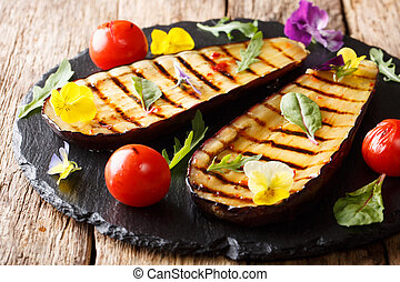 delicious healthy grilled aubergines and tomatoes with herbs and edible flowers close-up. horizontal