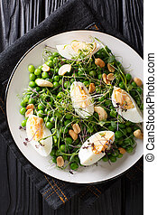 delicious healthy salad of green peas, micro greens, nuts and cooked eggs close-up on a plate. Vertical top view