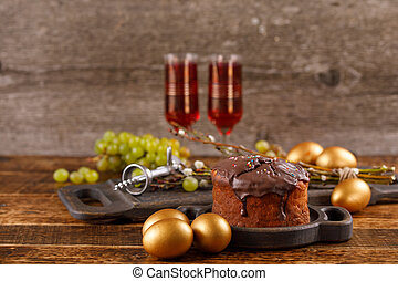 Delicious home-made Easter cake in chocolate glaze, vintage glasses with red wine and traditional painted eggs. A beautiful Easter still life in a rustic style.