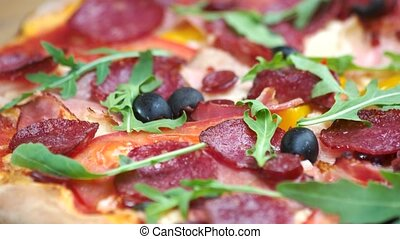 Delicious Italian pizza. Sausages, arugula and olives.
