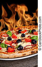 Delicious Italian pizza served on wooden table with flames ...