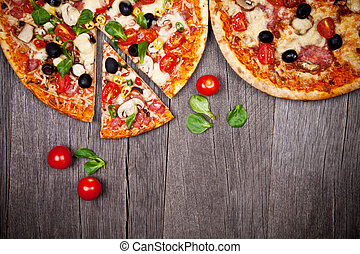 Delicious Italian pizzas served on wooden table