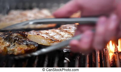 Delicious juicy pork meat steaks cooking on the grill on ...