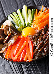Delicious Korean food Bibimbap with beef, yolk, vegetables, mushrooms and rice close-up in a bowl. vertical