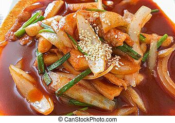Delicious Korean spicy tteokbokki. The image of spicy tteokbokki on wood background
