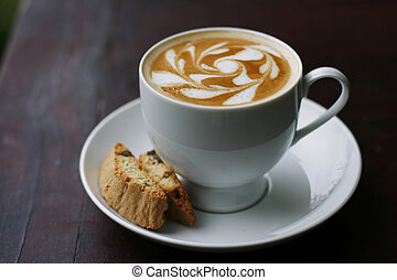 A delicious latte with a professional coffee art swirl design in a cup on a saucer with a decorative biscotti biscuit.