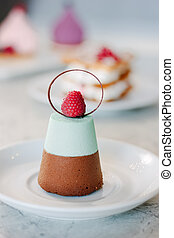 Delicious layered dessert cake with chocolate, souffle and raspberry.
