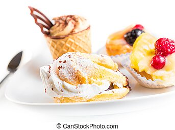 delicious little cream cake near cake with chocolate and fruit